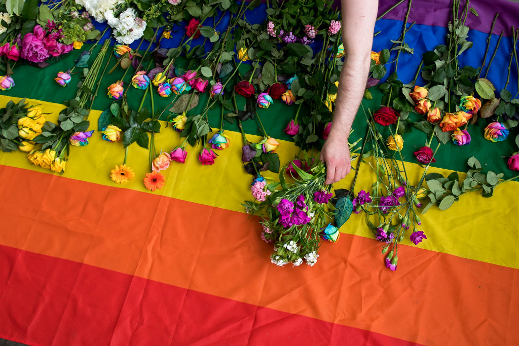 Demonstrators lay roses on a rainbow flag as they protest over an alleged crackdown on gay men in Chechnya outside the Russian Embassy in London on June 2, 2017.  Russian Foreign Minister Sergei Lavrov on May 30 insisted there were